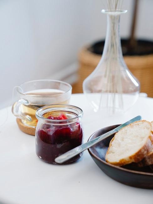 Dżem truskawkowy w małym słoiczku obok herbaty i talerza z pieczywem