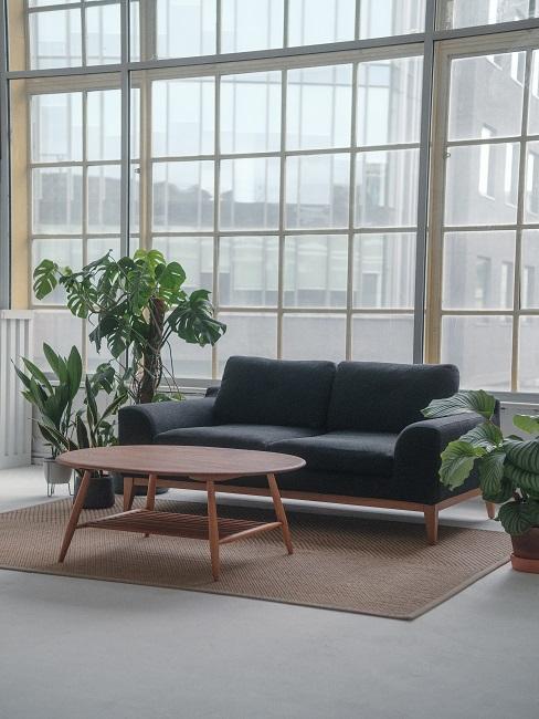 Stół drewniany w salonie z wysokimi oknami