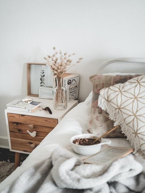 Stolik nocny z drewna z dodatkiem bieli obok łóżka