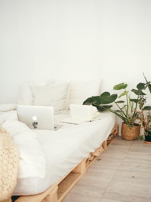 Łóżko z palet z jasną pościelą i laptopem na materacu