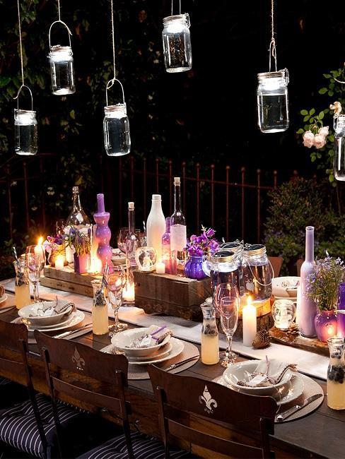 stół w ogrodzie wieczorem w stylu prowansalskim z fioletowymi akcentami i romantycznym oświetleniem