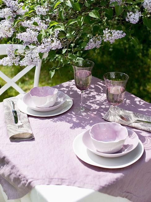 biały stół w ogrodzie z fioletowym obrusem i bzem w stylu prowansalskim