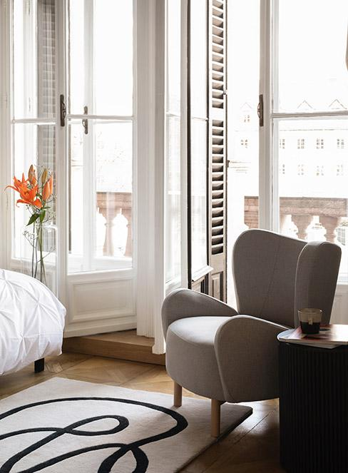 fotel uszak obok wyjścia na balkon we francuskiej kamienicy