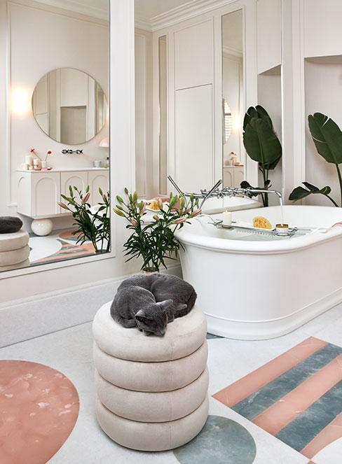 jasna łazienka z sztukaterią na ścianie z dużą wanną i dekoracjami glamour