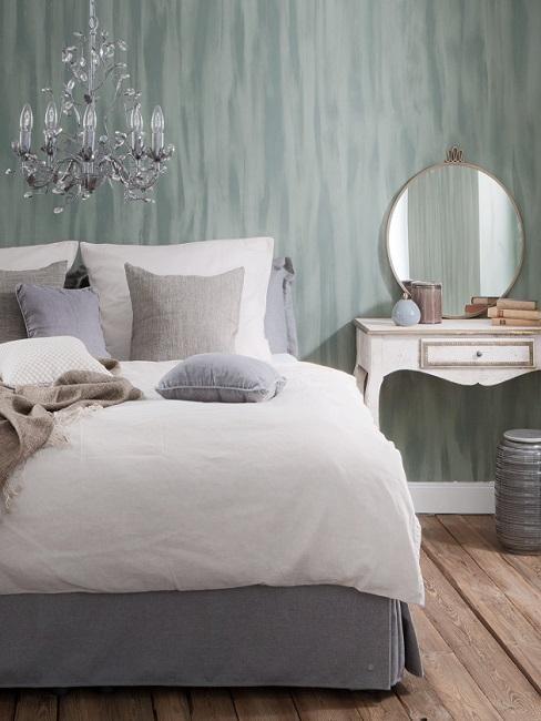 sypialnia w stylu prowansalskim z szarozieloną ścianą i srebrnym żyrandolem