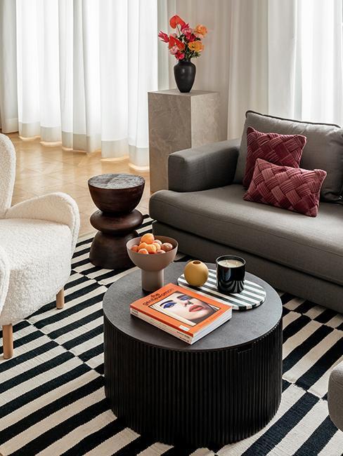 zbliżenie na ciemny drewniany stolik z na czarnobiałym dywanie przy szarej sofie z poduszkami bordo