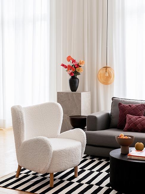 biały fotel uszak boucle przy szarej sofie w modnym wnętrzu