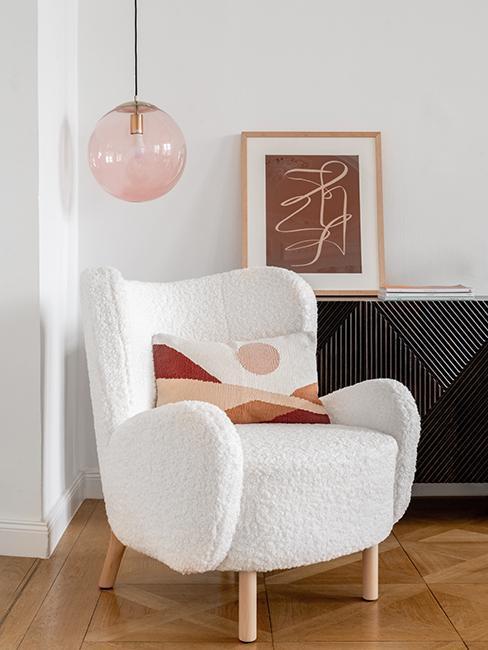 fotel uszak boucle pod różową lampą wiszącą w modnym wnętrzu