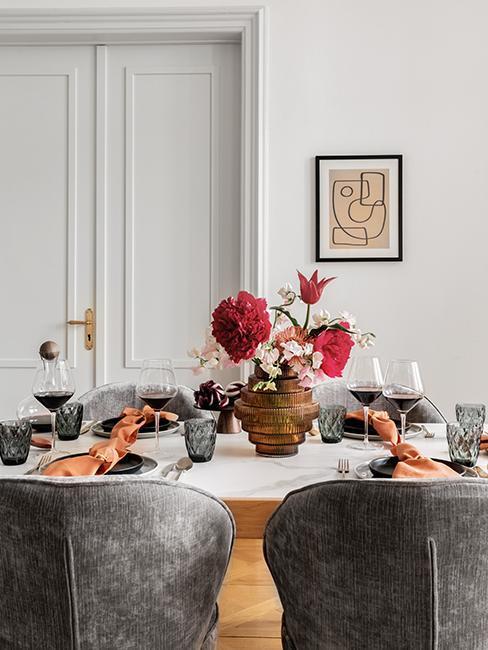 zbliżenie na bursztynowy wazon z kwiatami na białmy stole przy którym stoją szare krzesła