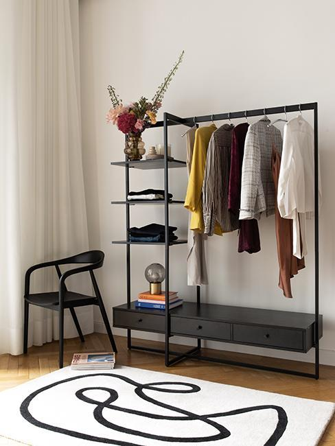 czarny wieszak na ubrania obok ciemnego krzesła w stylu japandi obok jasnego dywanu z graficznym wzorem