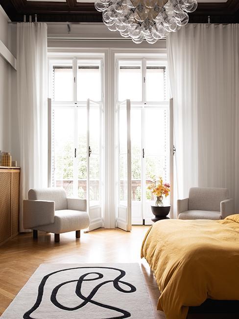 jasna sypialnia w modnym wnętrzu w stylu francuskim z fotelem boucle i łóżkiem, na którym jest żóta narzuta