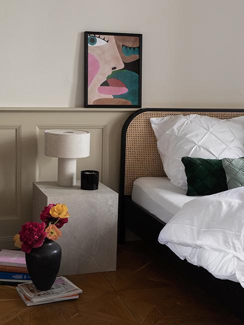 zbliżenie na łóżko z zagłówkeim z plecionki wiedeńskiej obok stolika z imiatacji betonu