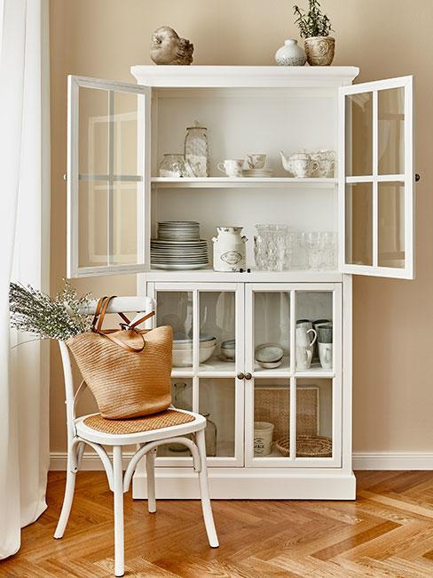 Biały kredens obok białego drewnianego krzesła, na którym stoi kosz w kuchni prowansalskiej