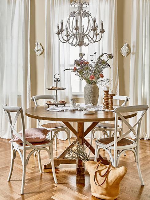 Okrągły drewnainay stół przy którym stoją białe drewniane krzesła w stylu prowansalskim