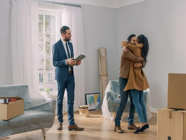 Szczęśliwa para w nowym mieszkaniu w towarzystwie pośrednika nieruchomości
