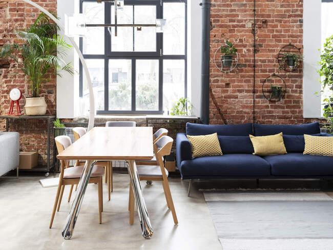 Salon z ceglaną ścianą, granatową sofą i drewnianym stołem