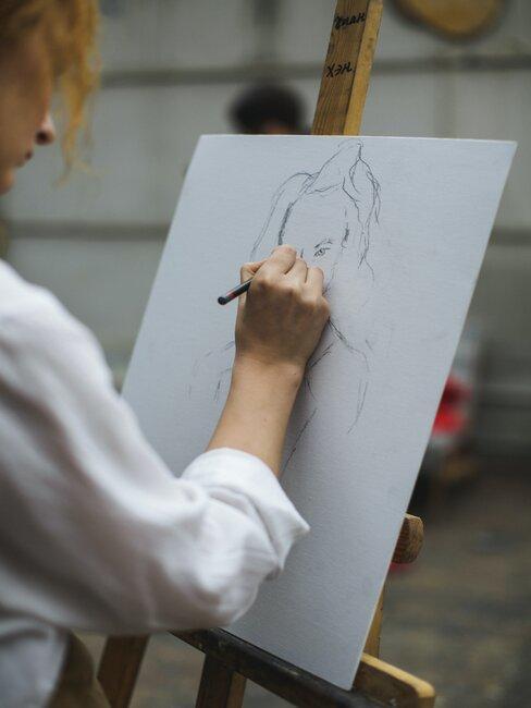 Kobieta rysuje postać na dużej karcie papieru