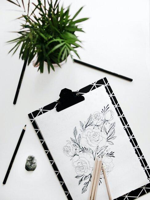 rysunek bukiet kwiatów zrobiony ołówkiem na czarnej podkładce na białym stole obok zielonej rośliny w doniczce