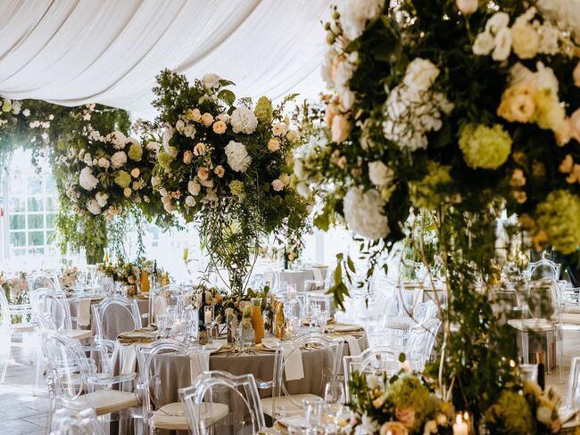 Dekoracje kwiatowe na przyjęciu weselnym w plenerowym namiocie