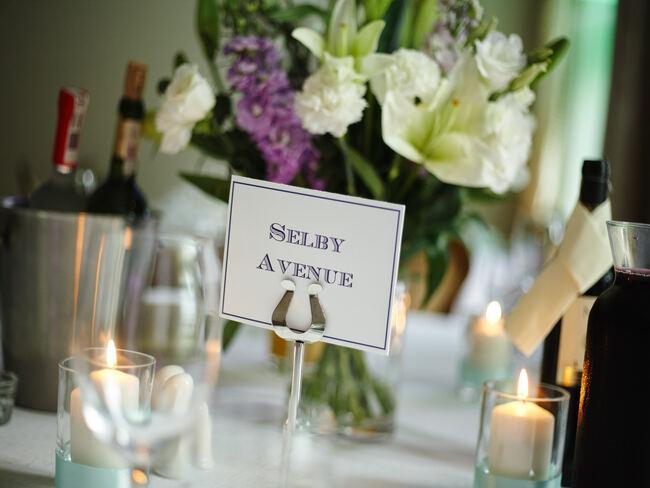 Kwiaty, świeca i winietka na stole weselnym