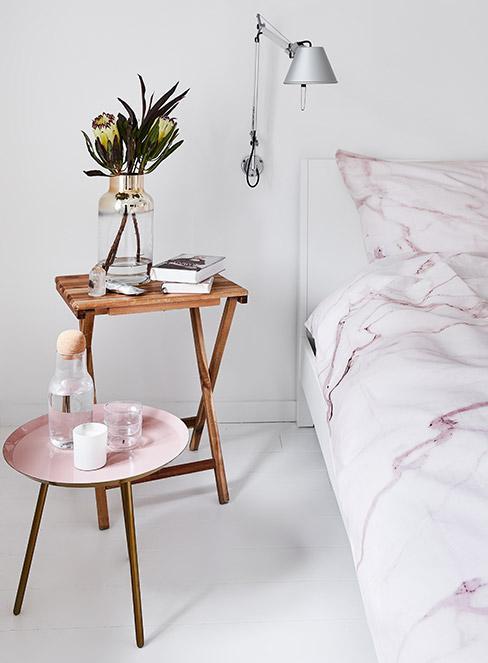 woda a wkarafce na różowym stoliku w sypialni