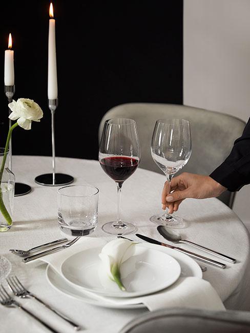 dwa kieliszki z czerwonym winem na elegancko zastawionym stole z białym obrusem i srebrnymi sztućcami