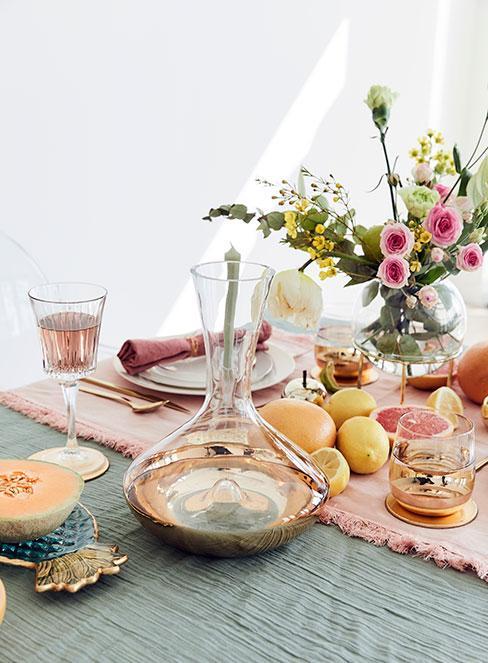 kolorowo zastawiony stół z szklaną karafką ze złotym dnem i, świeżymi owocami i winem rose