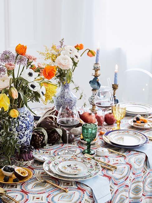barokowo udekorowany stół z kwiatami w baiło niebieskich wazonach i elegancką zastawą