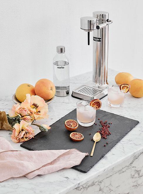 drionk z grejpfrutem i ginem na stole kuchennym z marmuru obok jasnych kwiatów