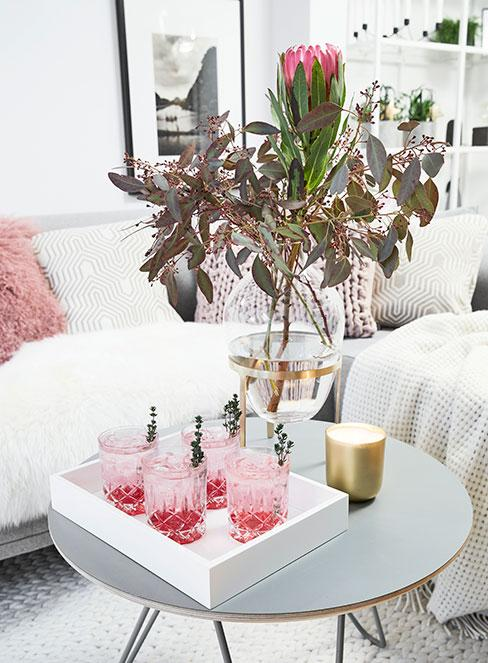cztery kieliszki z różowym drinkiem z lawendą na białej tacy na stoliku pomocniczym w salonie glamour