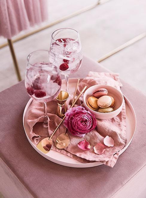 pięknie podany drionk z malinami n a złotej tacy z różami i makaronikami