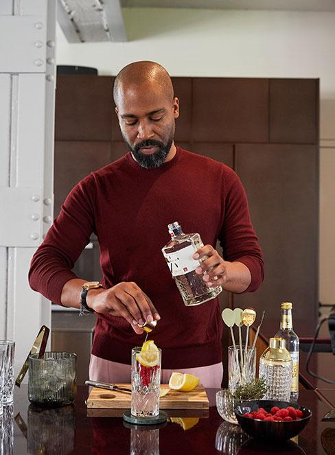 mężczyzna robiący koktajl z wódką i cytryną