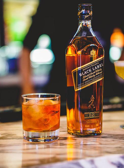 Butelka alkoholu z szklanką obok