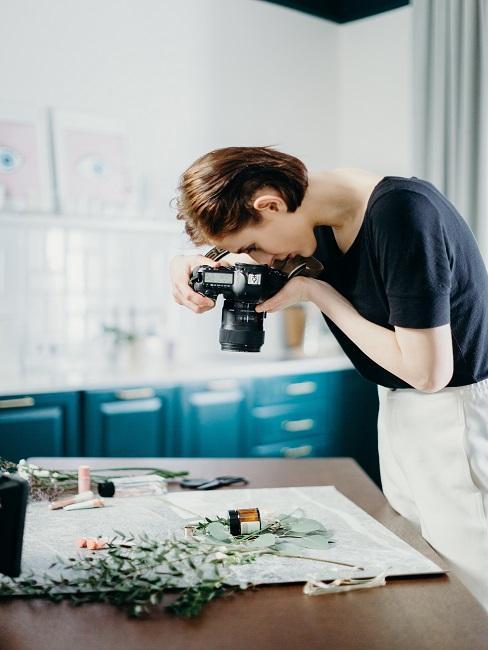 Fotografia artystyczna: kobieta fotografująca przedmiotu na stole
