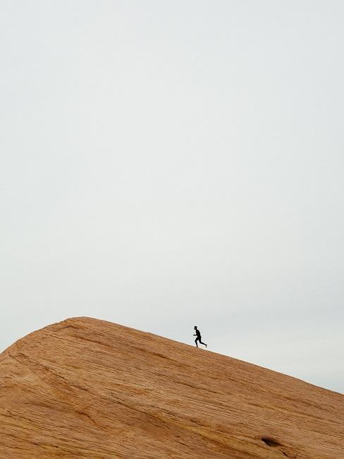 W dali biegnąca postać po piasku
