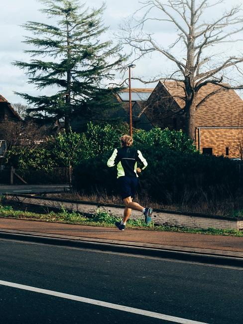Mężczyzna, który biegnie obok domków jednorodzinnych