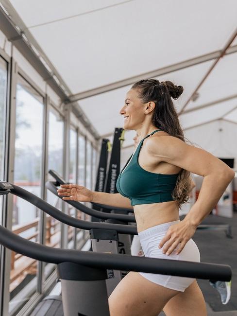 Co daje bieganie: kobieta biegnąca na bieżni na siłowni