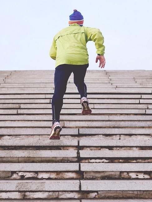 Mężczyzna w żółtej kurtce biegnący po schodach