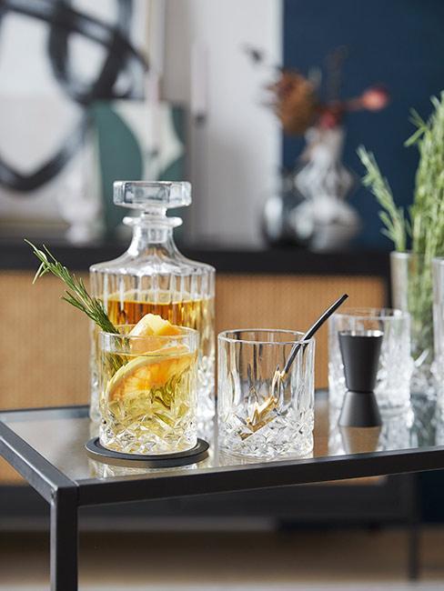 Karafka z szklanką na stoliku barowym z szklankami na whisky