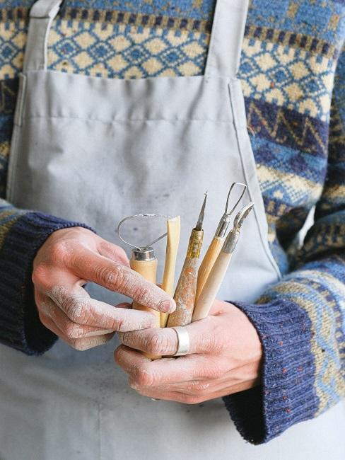 Mężczyzna trzymający narzędzia do garncarstwa