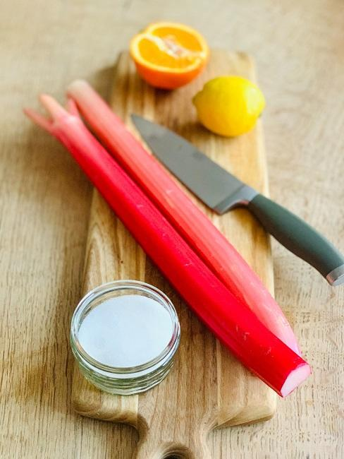 Łodyga rabarbaru na desce drewnianej z nożem i cukrem