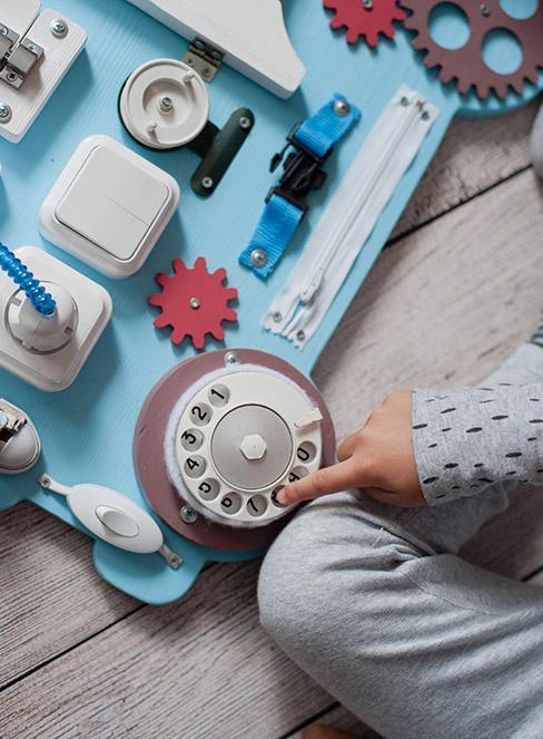 zbliżenie na rękę dziecka bawiącego się przy tablicy manipulacyjnej