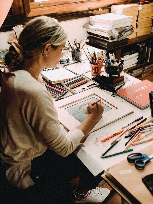 Kobieta malująca obraz przy biurku