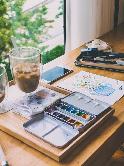 Przybory do malowania i stojąca obok mrożona kawa