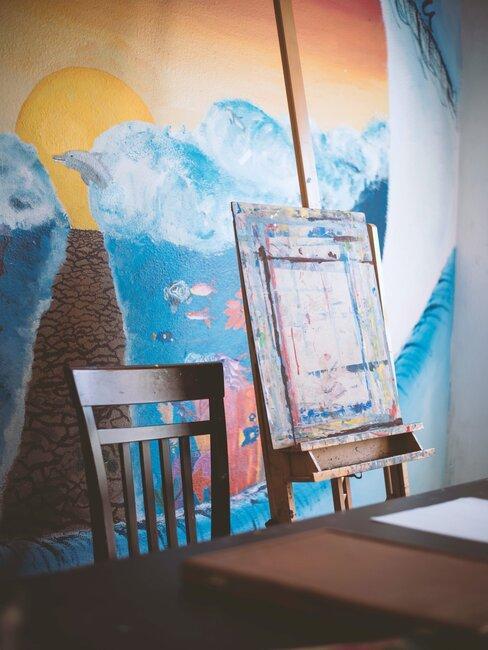 Ściana udekorowana malunkiem, obok niej sztalugi do malowania