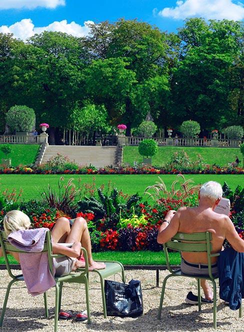 starsza para opalająca się na krzesłach w ogrodzie francuskim