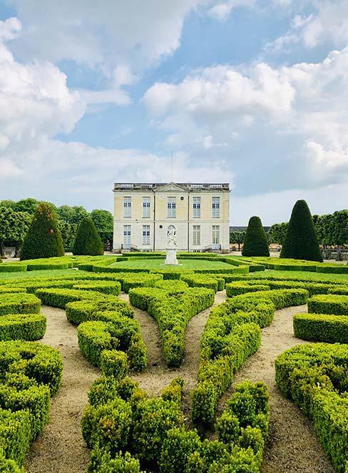 ogród francuski z żywopłotem z pałacem w tle