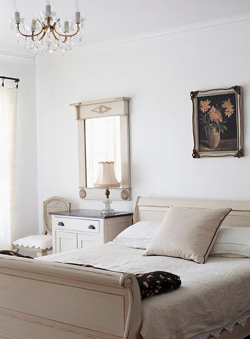 Beżowa sypialnia w stylu prowansalskim z bielonymi postarzonymi meblami w kolorze beżowym i obrazkiem z kwiatami na ścianie