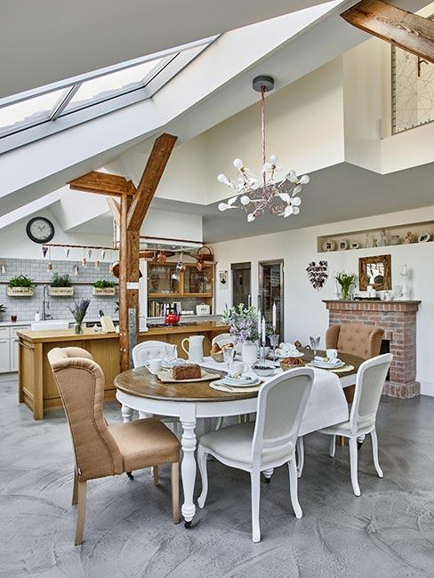 jadalnia z kuchnią na poddaszu w stylu prowansalskim z okrągłym białym stołem i tapicerowanymi krzesłami
