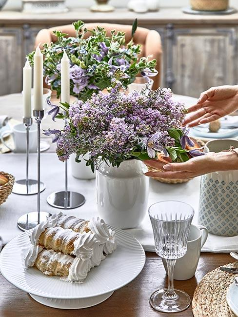 ciastka z kremem na stole w jadalni w stylu prowansalskim obok wazonu z bzem
